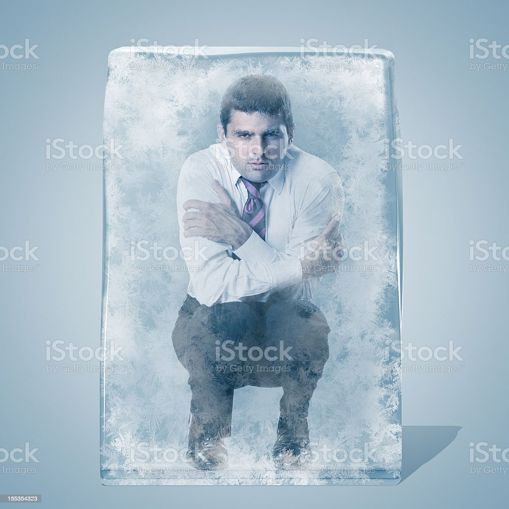 Businessman crouched frozen in an ice space royalty-free stock photo