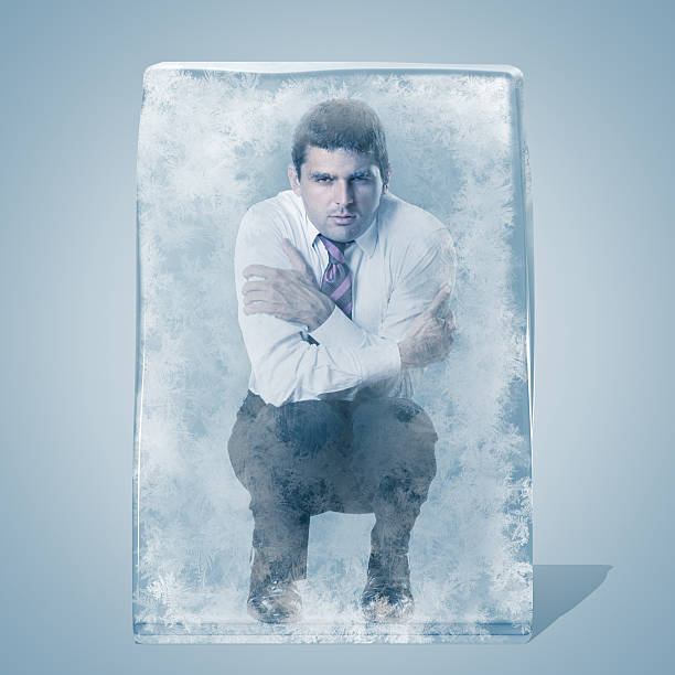 Businessman crouched frozen in an ice space stock photo