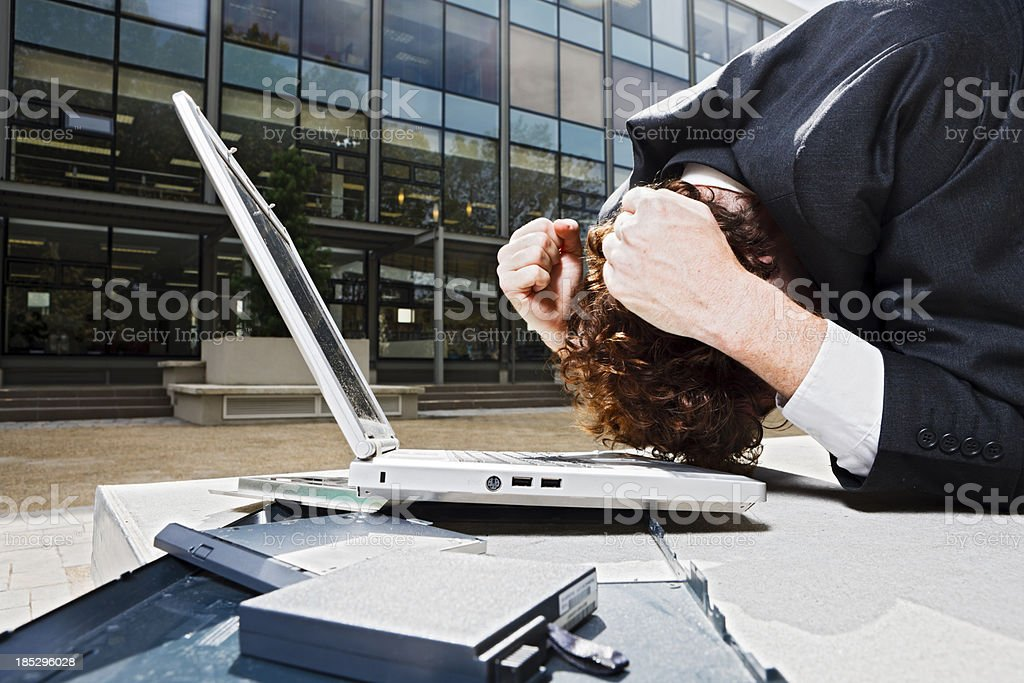 Businessman crouches with clenched fists beside broken laptop royalty-free stock photo