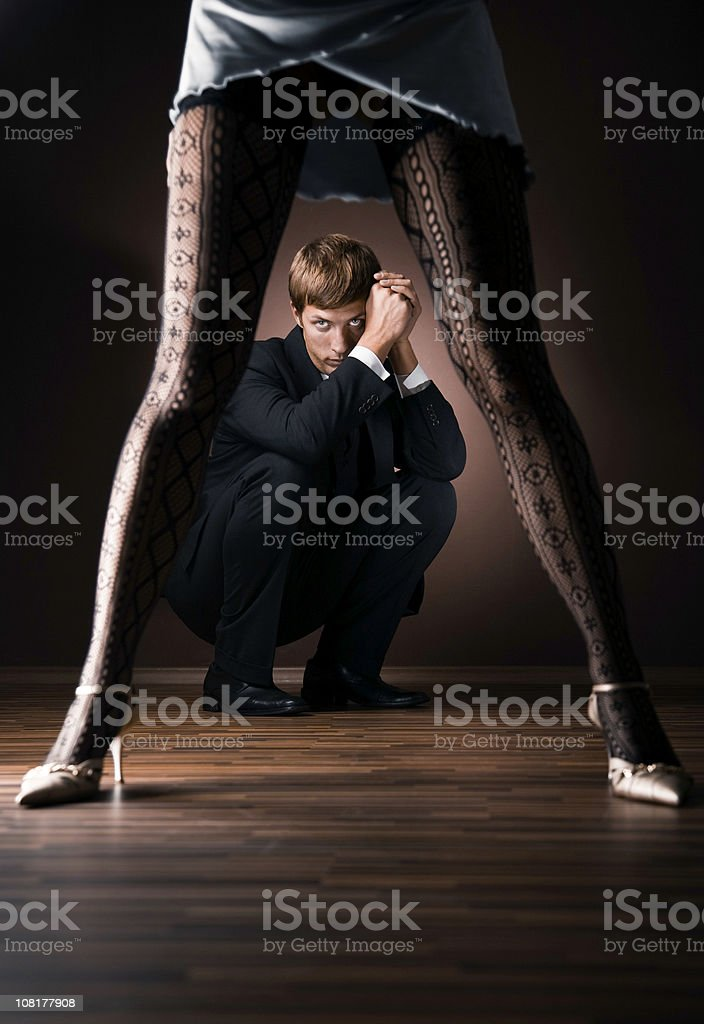 Businessman Crouching Behind Woman's Legs stock photo