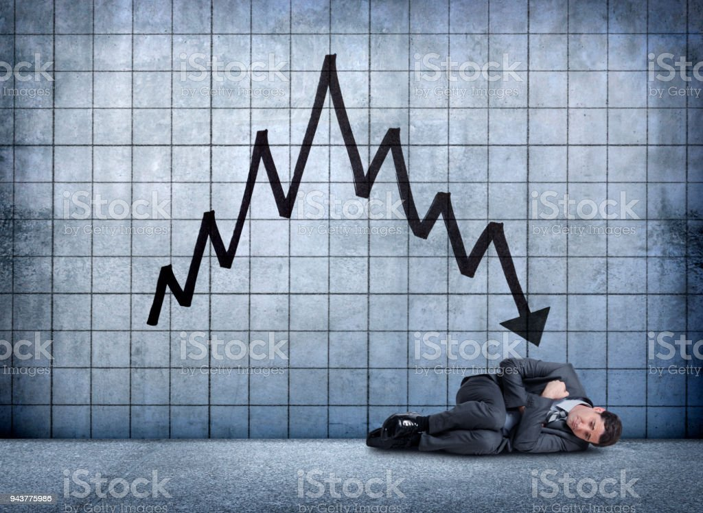 Businessman Curled Up In Fetal Position Distraught Over Falling Results stock photo