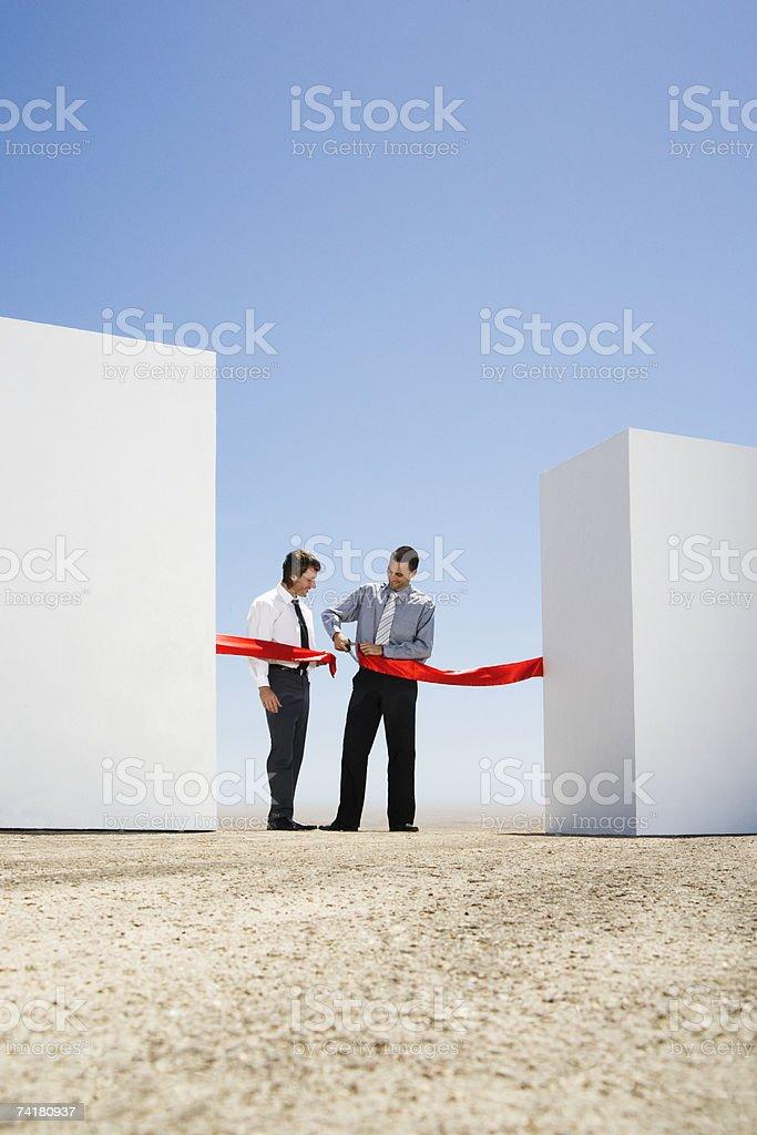 Um empresário de cortar uma fita vermelha ou fita entre duas Paredes foto de stock royalty-free