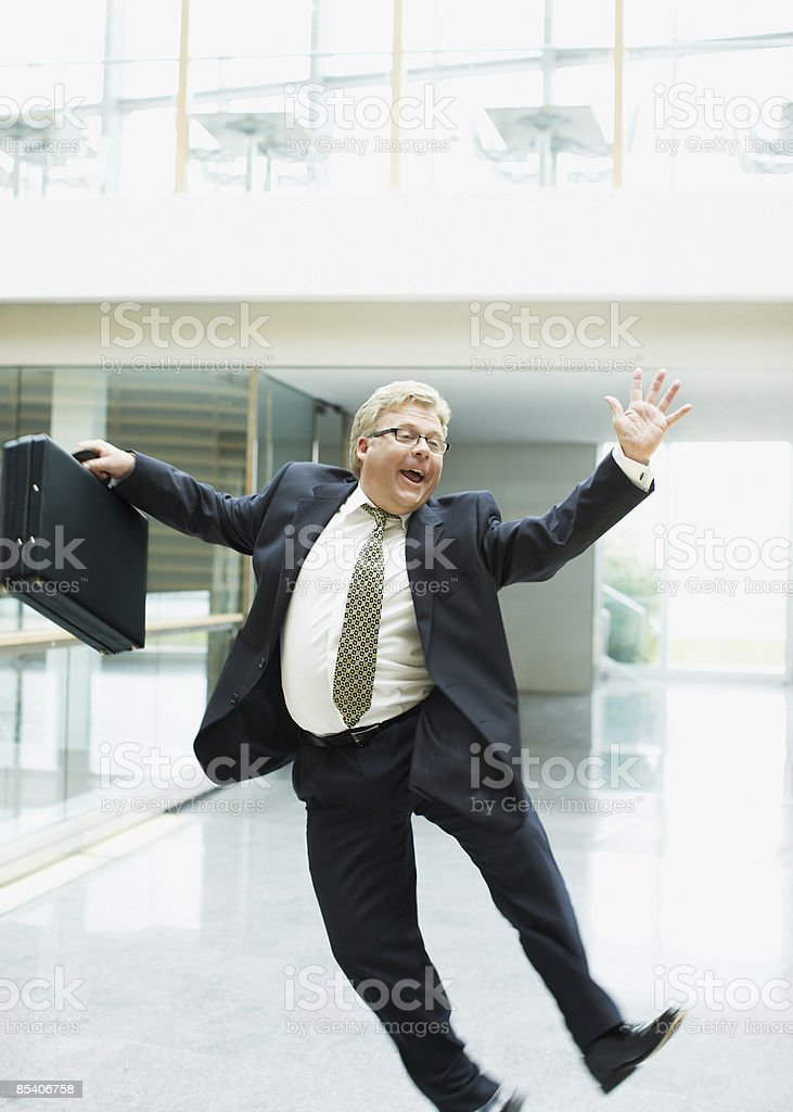 Businessman dancing in office lobby royalty-free stock photo