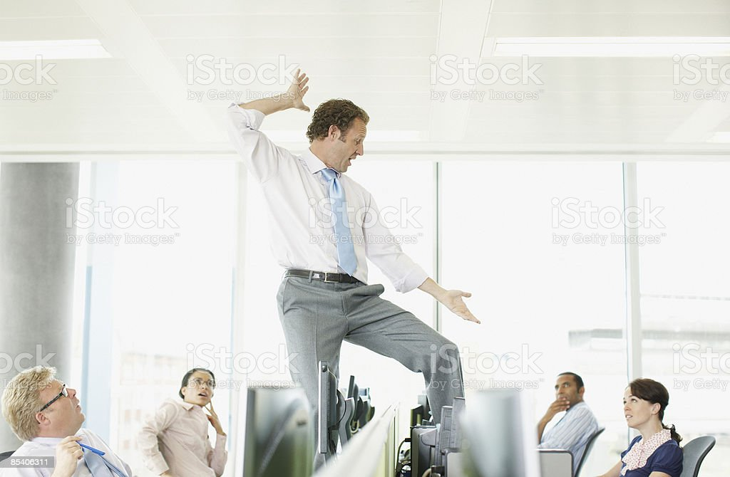 Businessman dancing on desk in cubicle stock photo