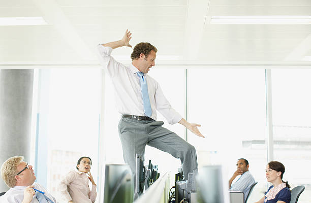 businessman dancing on desk in cubicle - arrogance stock pictures, royalty-free photos & images