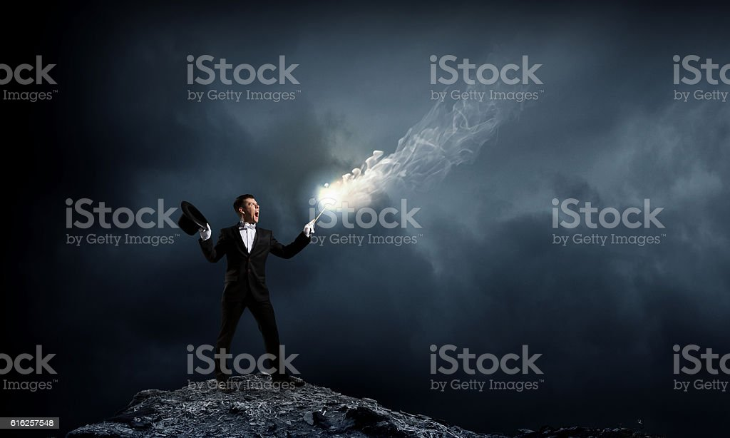 Businessman demonstrating magic . Mixed media stock photo