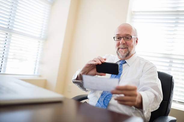 businessman depositing check via smartphone from his office - bank deposit slip stock pictures, royalty-free photos & images
