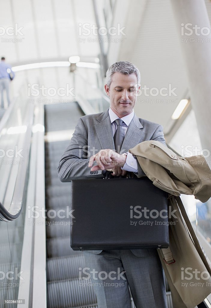 Businessman descending escalator and checking the time royalty-free stock photo