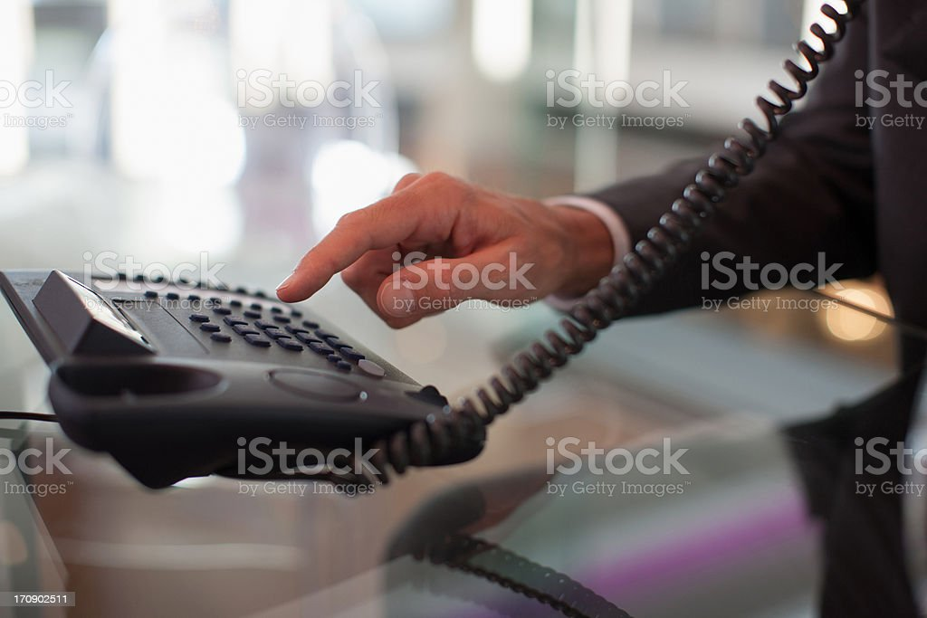 Businessman dialing telephone in office stock photo