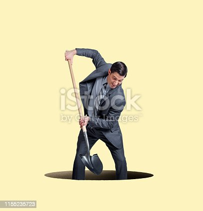 A businessman uses a shovel to dig himself into a hole isolated against a yellow background.