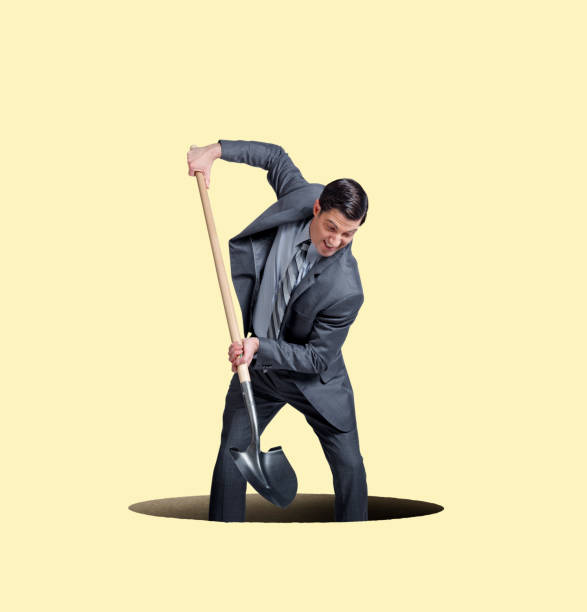 Businessman Digging A Hole For Himself stock photo
