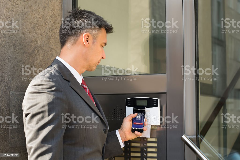 Businessman Disarming Security System Of Door With Smartphone royalty-free stock photo