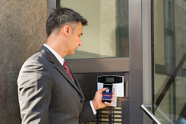 Businessman Disarming Security System Of Door With Smartphone stock photo