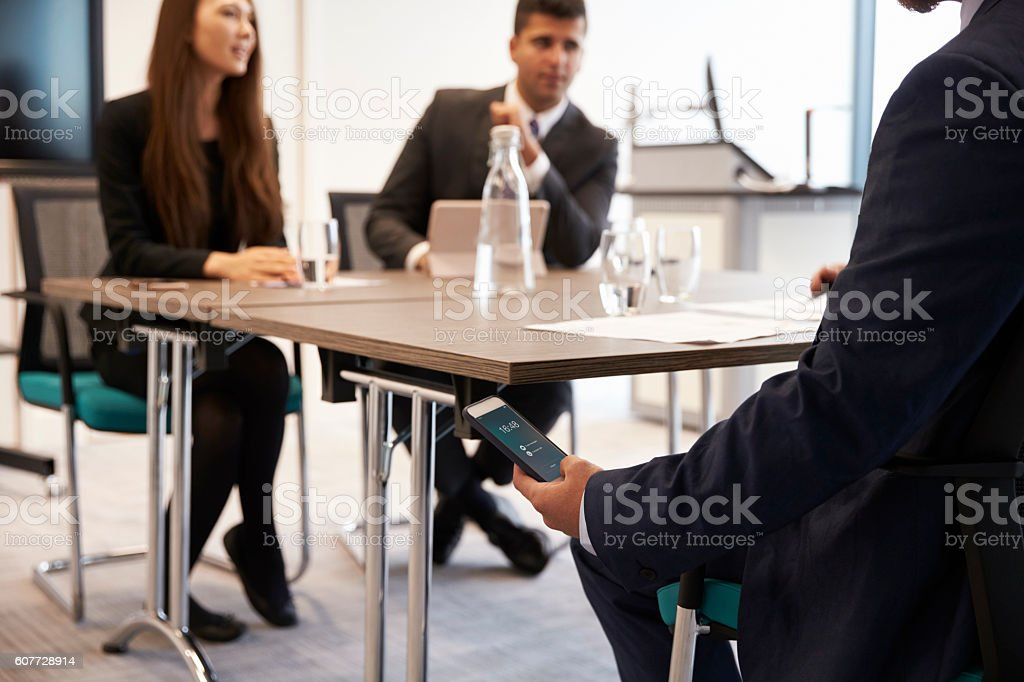 Businessman Discreetly Replying To Text Message During Meeting – Foto