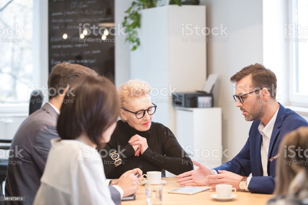 Businessman discussing future plans in meeting Mature businessman discussing future plans with his colleagues. Group of corporate business team having meeting in office. Active Seniors Stock Photo