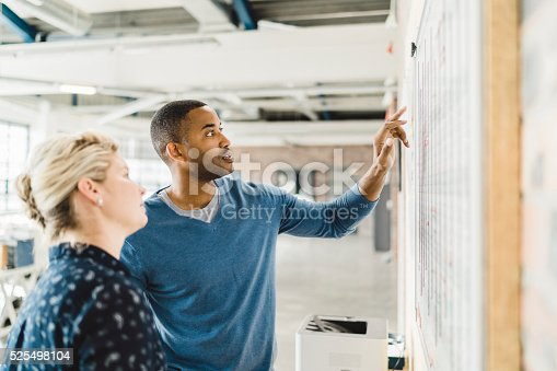 istock Businessman discussing with colleague over whiteboard 525498104