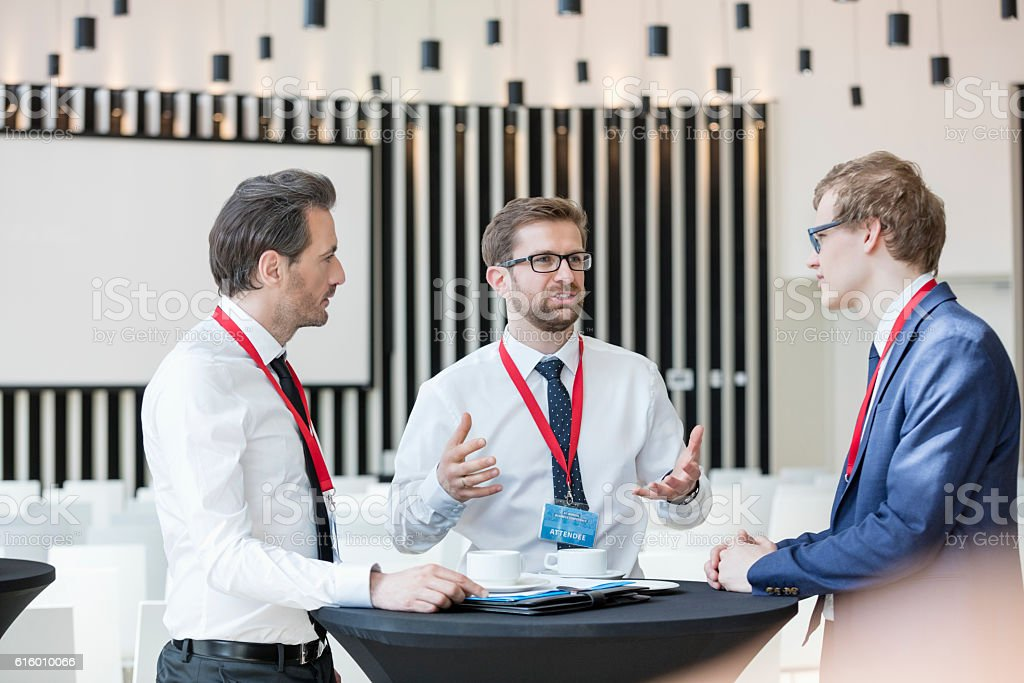Businessman discussing with colleagues during coffee break in convention center stock photo