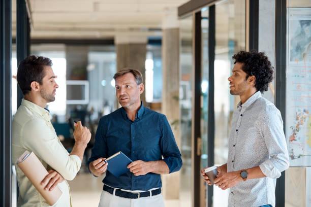 Unternehmer diskutieren mit Kollegen im Korridor – Foto