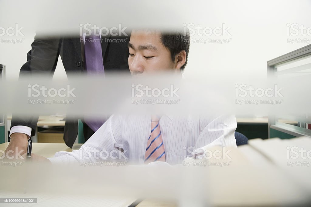 Businessman discussing with his colleague in office, view through window blinds foto de stock libre de derechos