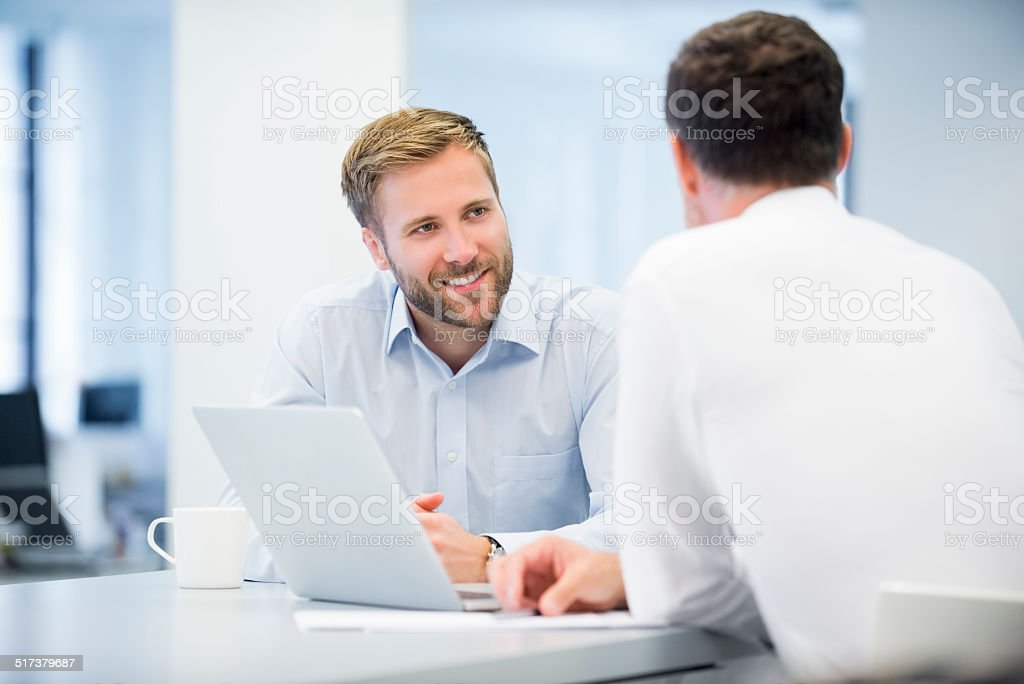 Businessman Discussing With Male Colleague stock photo