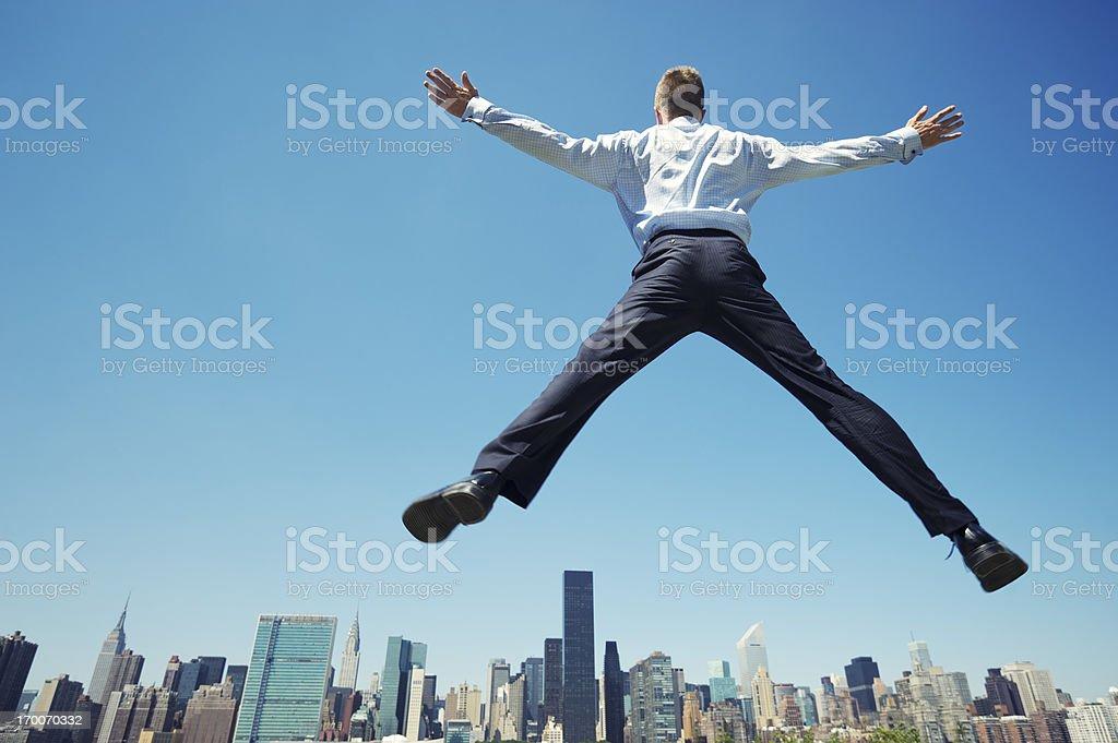 Businessman Does Big Leap Above City Skyline stock photo