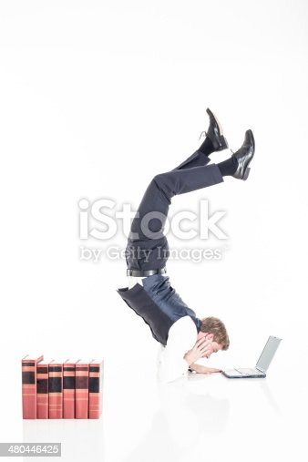 istock businessman doing a scorpion while working 480446425