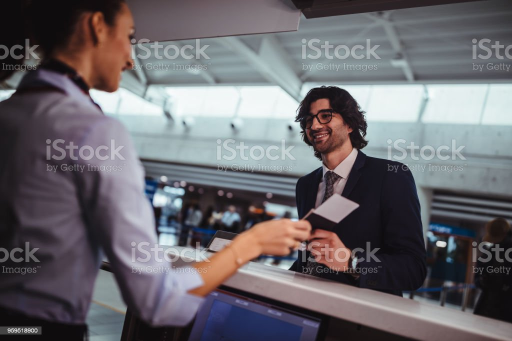 Businessman doing check-in and getting boarding pass at airport stock photo