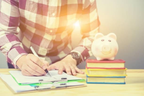 geschäftsmann, der finanzen mit dem taschenrechner und dem schreiben von notizen über die kosten jahres-und kostenkonto bei home office erledigt. - kindergeldantrag stock-fotos und bilder
