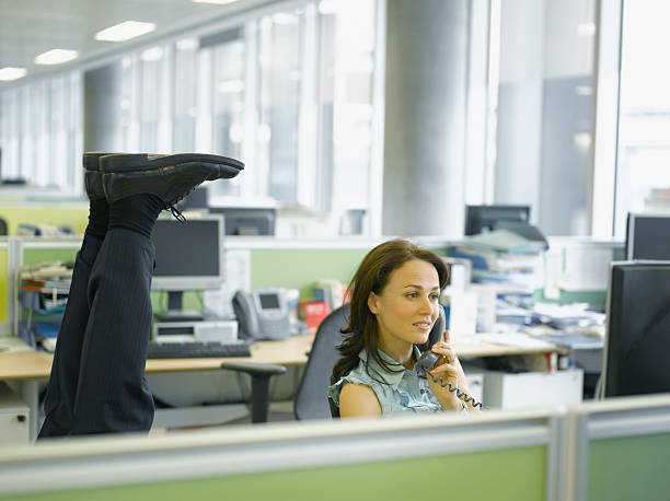 Businessman doing headstand in office stock photo