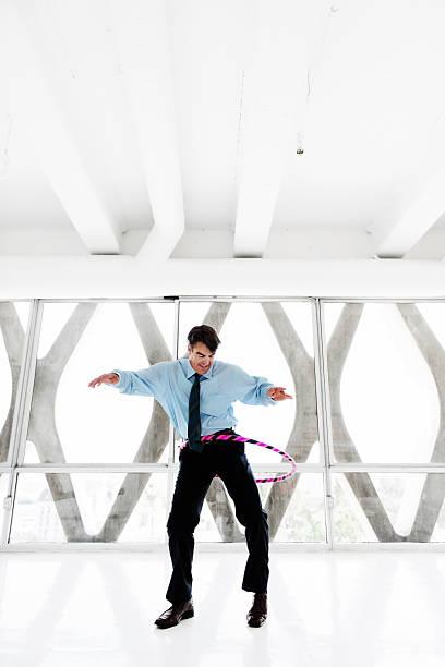 geschäftsmann bei hula-hoop - hula hoop workout stock-fotos und bilder