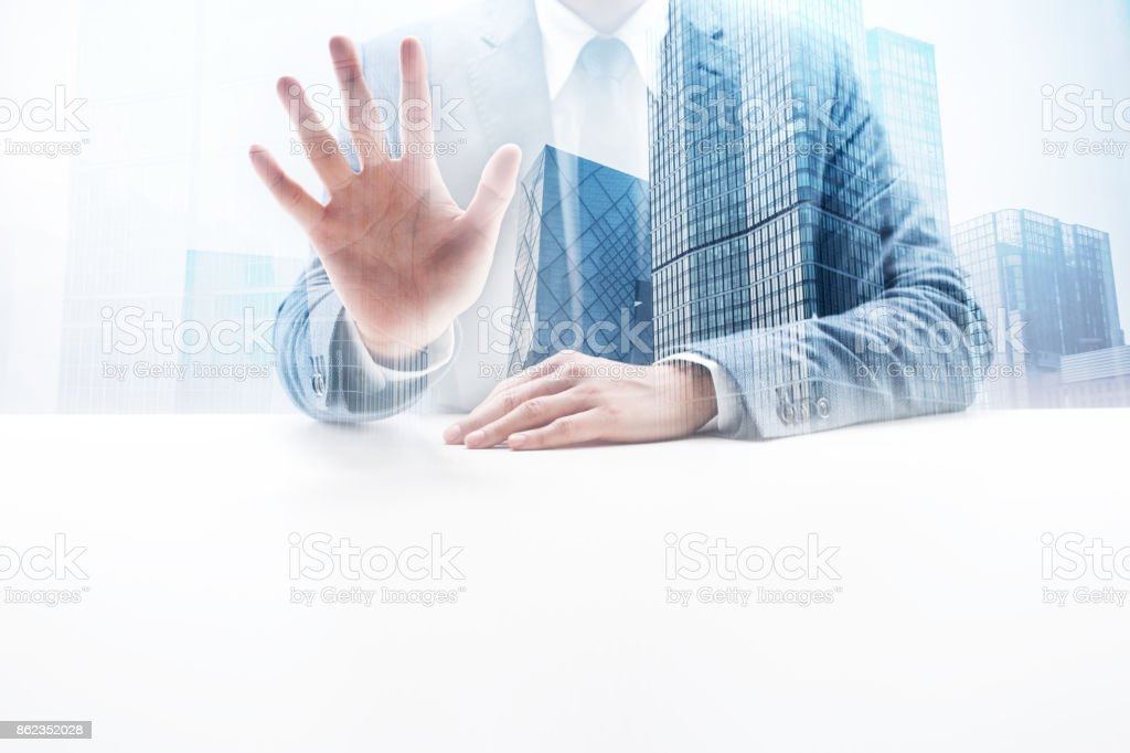 Businessman sitting by the desk doing number five hand sign with...