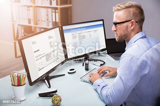 istock Businessman Doing Online Banking On Computer 949178440