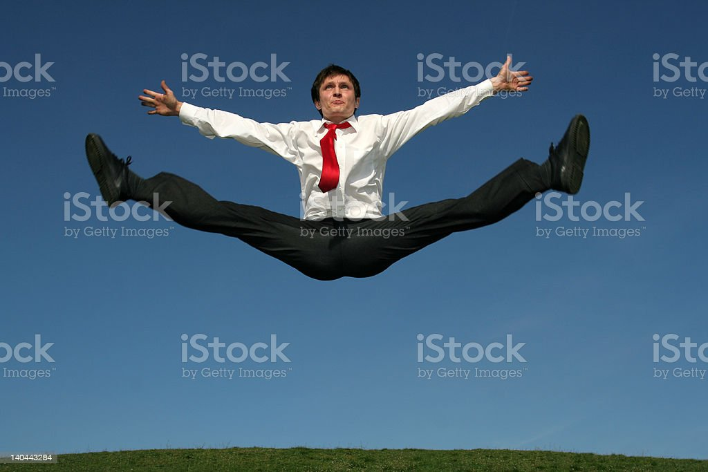 Businessman doing splits in mid-air royalty-free stock photo