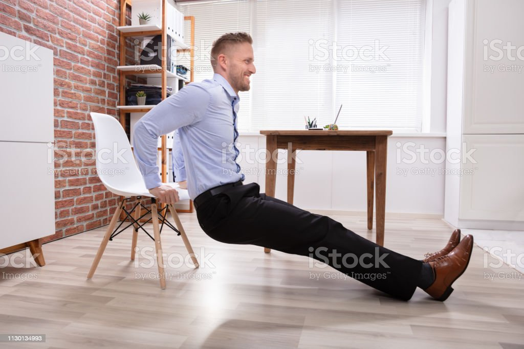 Businessman Doing Triceps Dips In Office Happy Young Businessman Doing Triceps Dips In Office Active Lifestyle Stock Photo