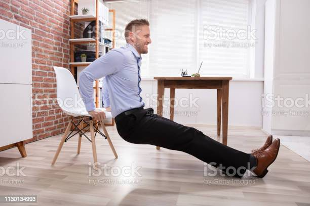 Businessman Doing Triceps Dips In Office Stock Photo - Download Image Now