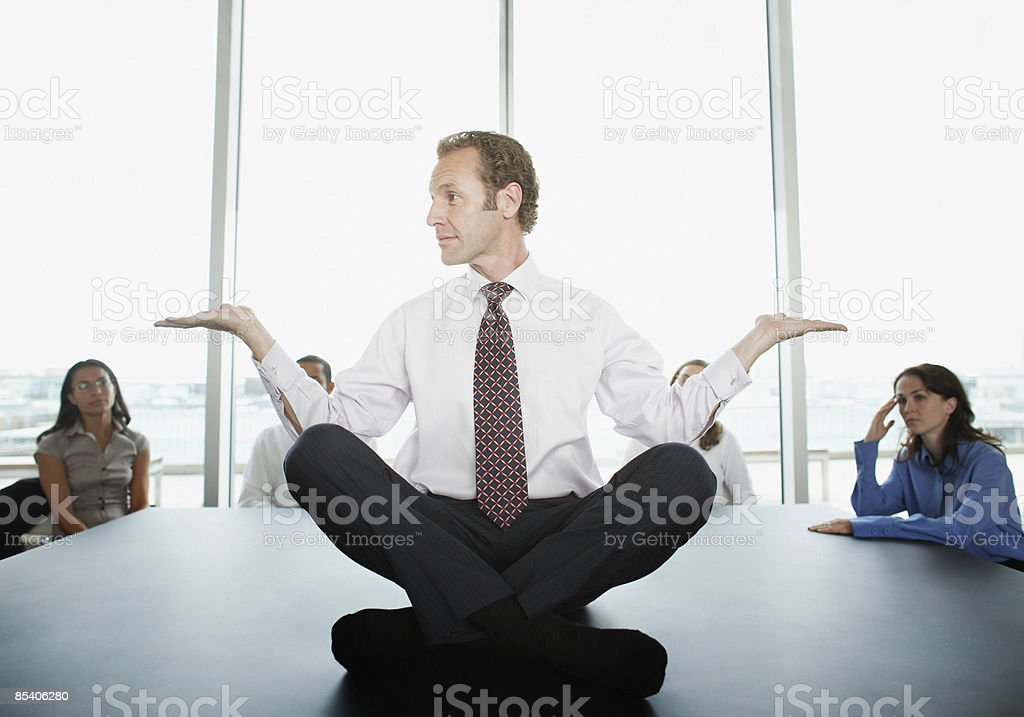 Businessman doing yoga in conference room stock photo