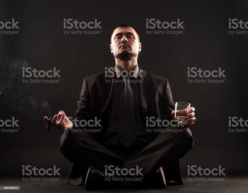 Businessman doing yoga with cigar and whiskey royalty-free stock photo