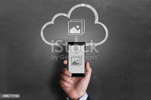istock Businessman downloading pictures from cloud storage 498273164