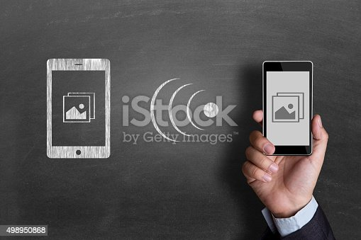 istock Businessman downloading pictures from cloud storage 498950868