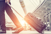Businessman drag luggage and hold suit in city outdoor on building background. Concept of business trip and work life balance. Image processing vintage color.