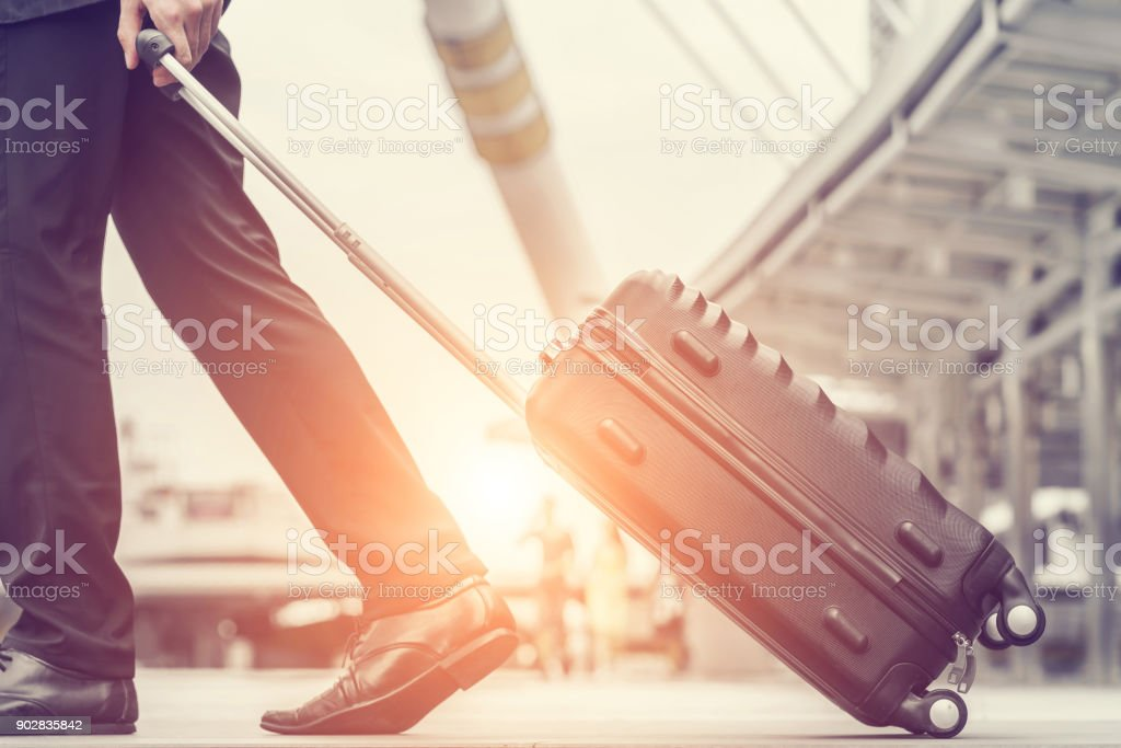 Businessman drag luggage and hold suit in city outdoor on building background. Concept of business trip and work life balance. Image processing vintage color. stock photo