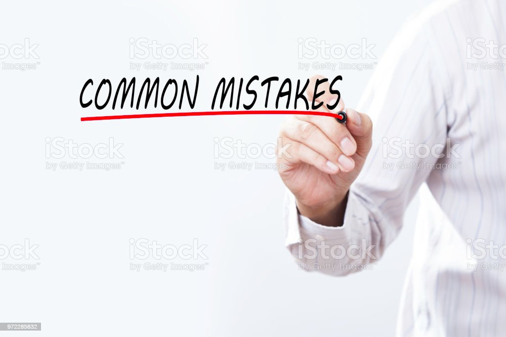 Businessman draw COMMON MISTAKES word with red marker on transparent wipe board, business concept. Training Planning Learning Coaching Business Guide Instructor Leader concept. stock photo
