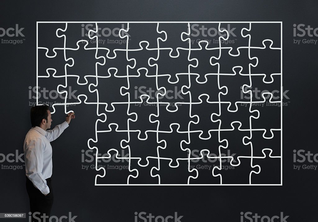 Businessman Drawing a Puzzle stock photo