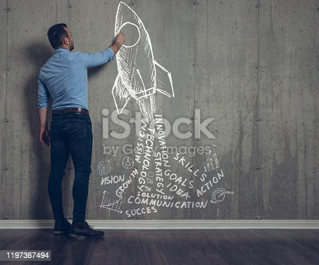 Businessman drawing a rocket with business words as engine smoke on a concrete wall.