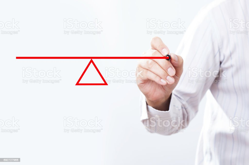 Businessman drawing a  seesaw to demonstrate the concept of a lever and fulcrum, of balance, equilibrium and equality. stock photo