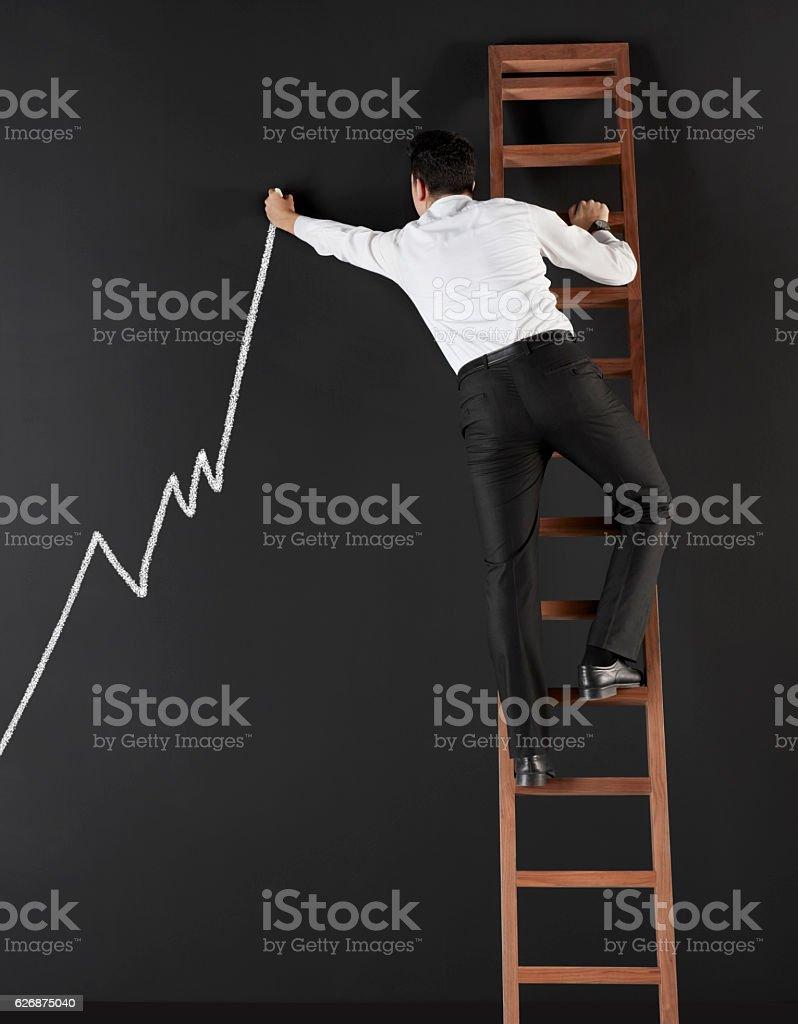 Businessman drawing an increasing graph stock photo