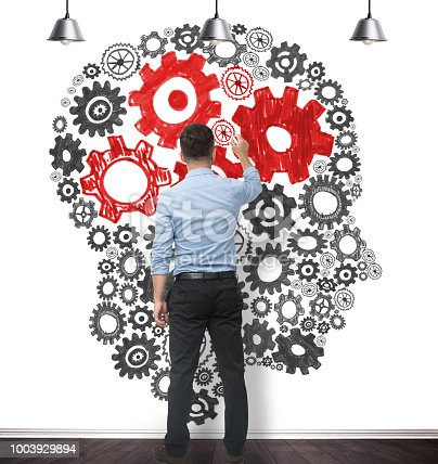 Businessman blue shirt drawing on the wall a human head out of gears. The brain part of the brain is in red