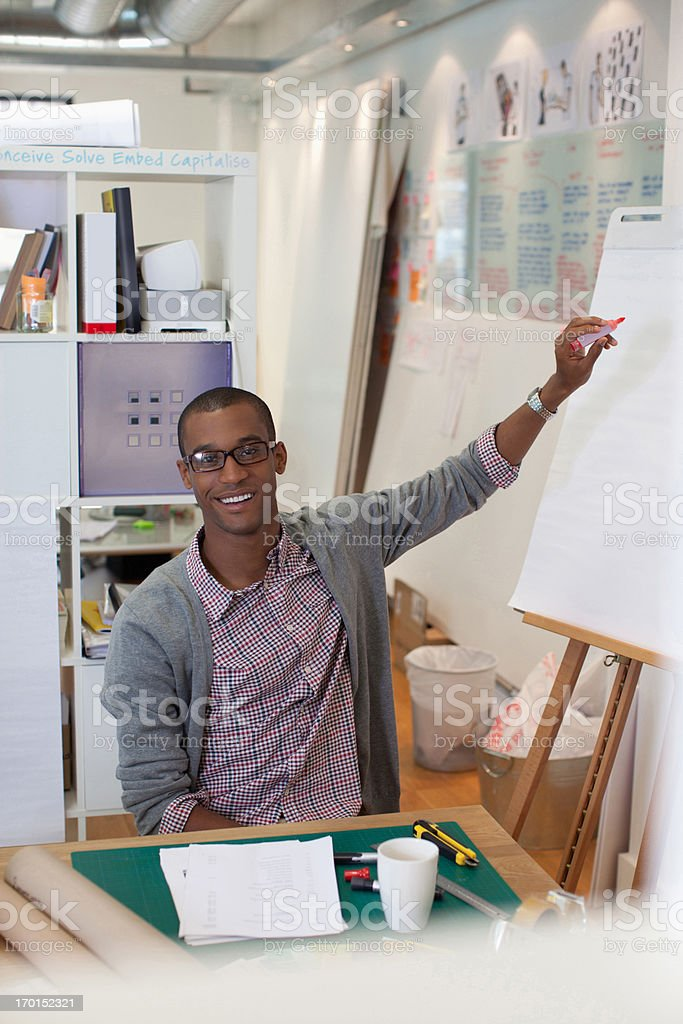 Businessman drawing diagram on flip chart in office royalty-free stock photo