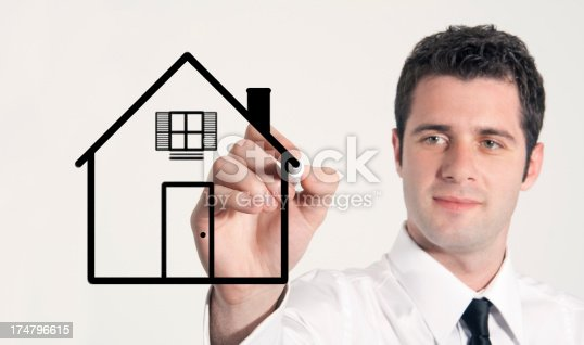 istock Businessman drawing house 174796615