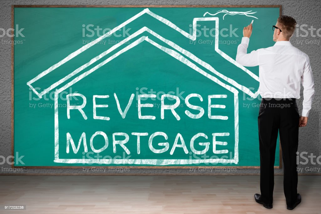 Businessman Drawing House With Reverse Mortgage Text stock photo